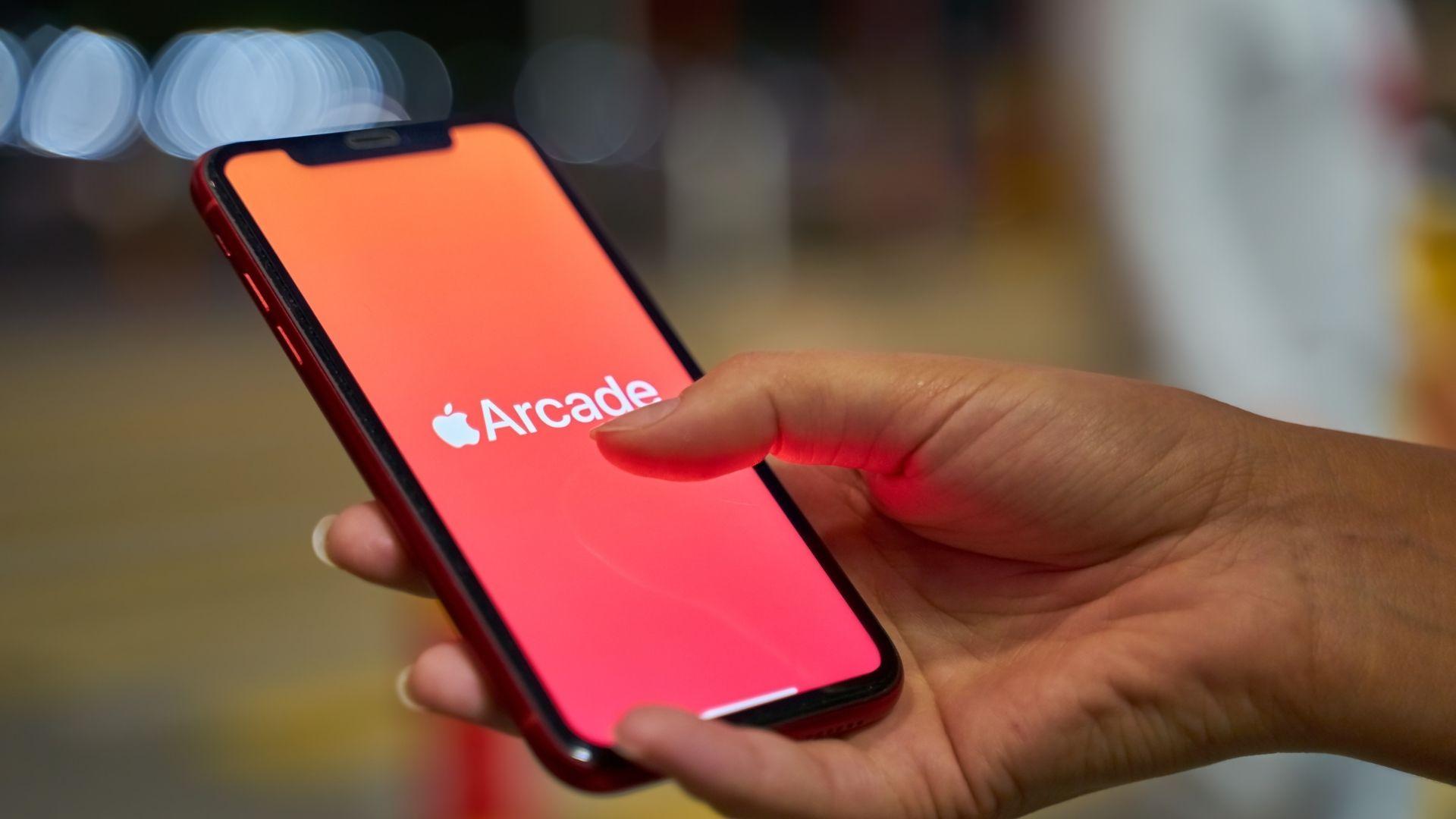 Mão de mulher segurando iPhone vermelho com Apple Arcade na tela