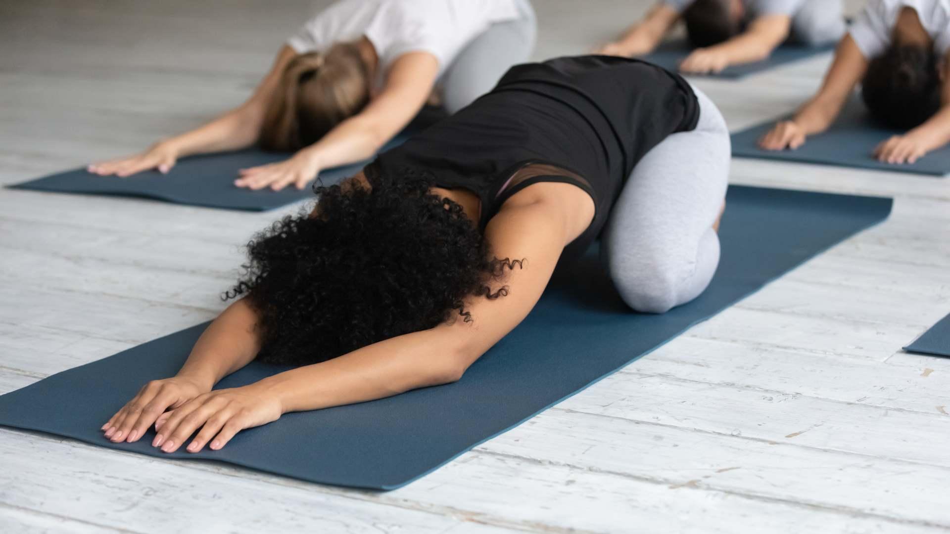 Pessoas fazendo postura de yoga em aula de yoga