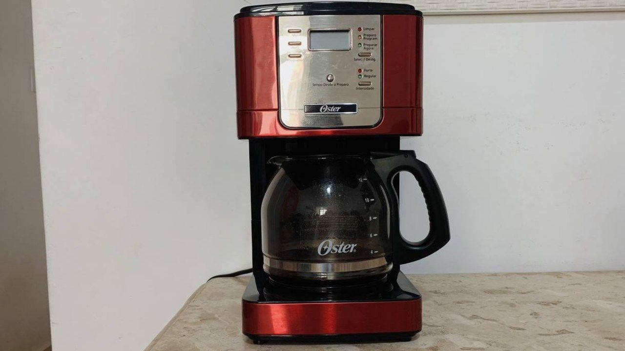 Cafeteira programável Oster Flavor vermelha apoiada em bancada de mármore com parede branca ao fundo