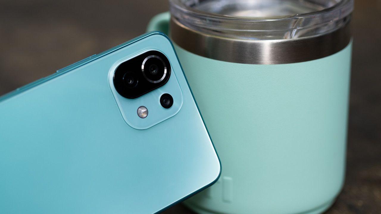 Imagem do celular Mi 11 Lite azul com traseira em destaque encostado em caneca
