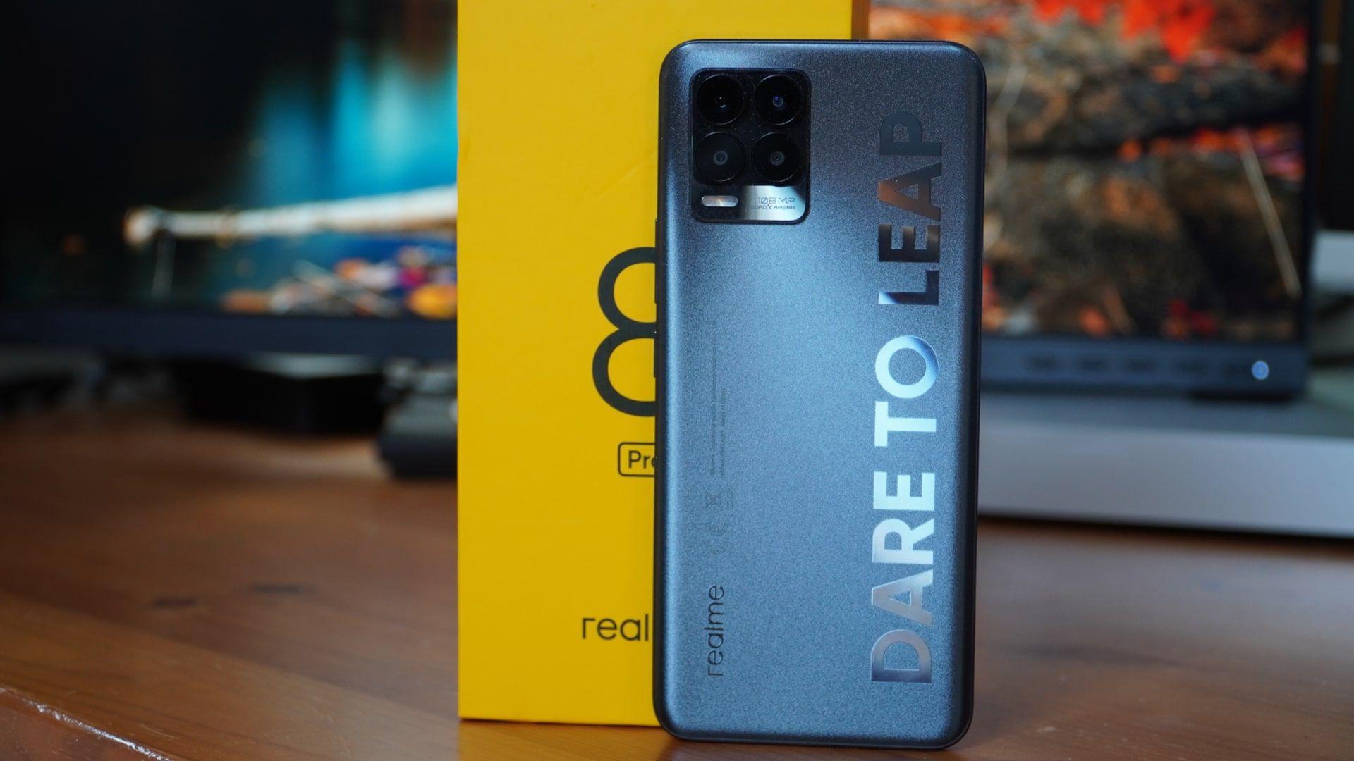 Celular Realme 8 Pro na cor cinza em pé, apoiado na caixa do smartphone