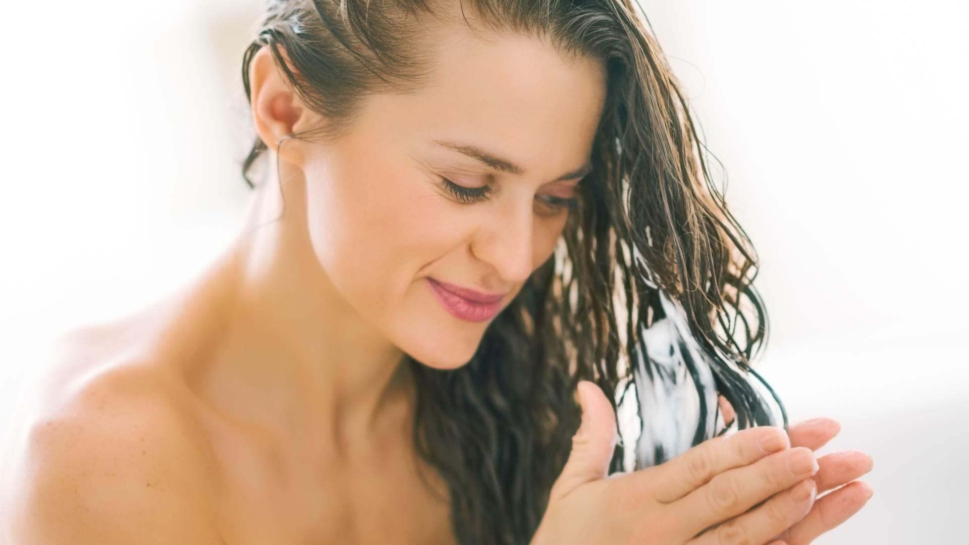 Mulher cuidando dos cabelos no banho
