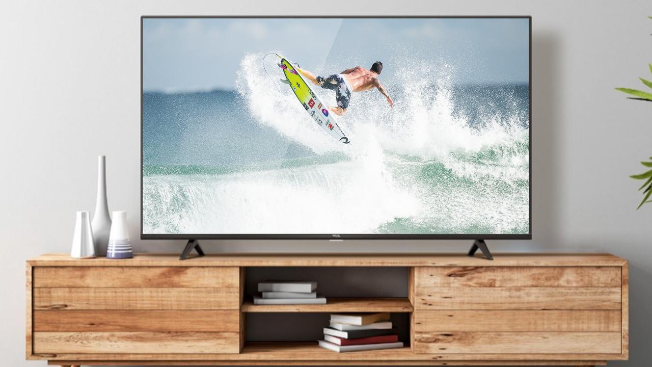 TV TCL P615 apoiada em rack de madeira clara com parede branca ao fundo