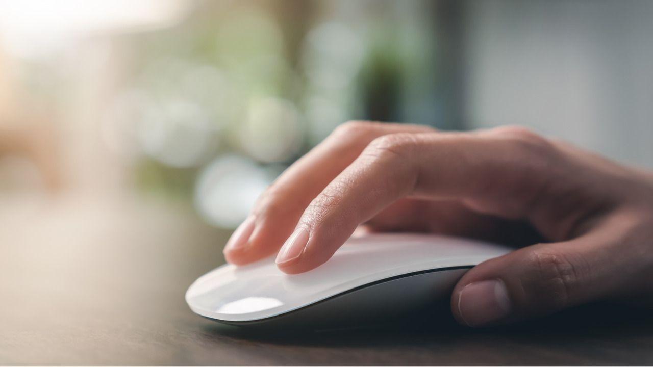 Mão em cima de um mouse Bluetooth branco e sem fio