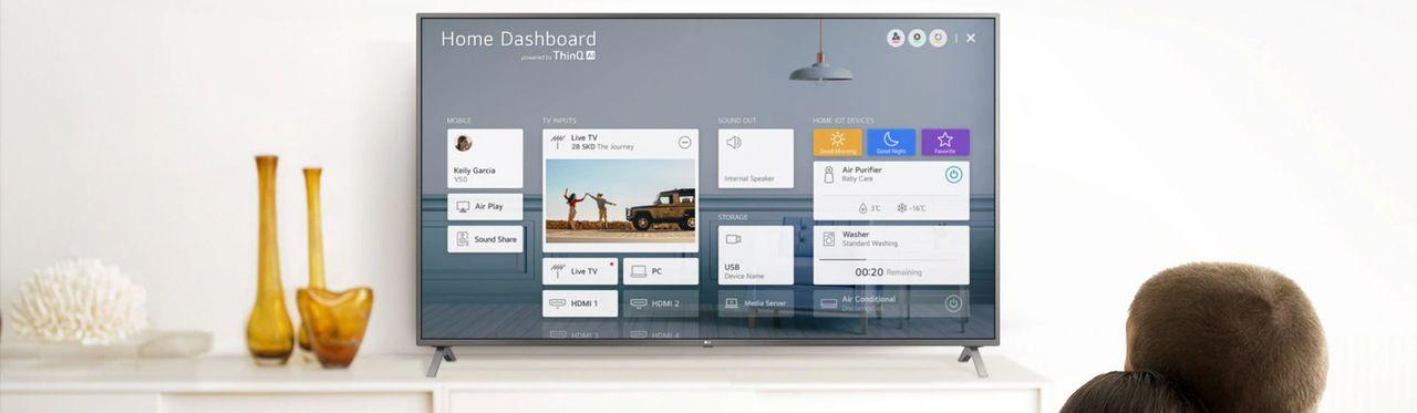 TV apoiada em móvel branco com menu de tarefas aberto na tela