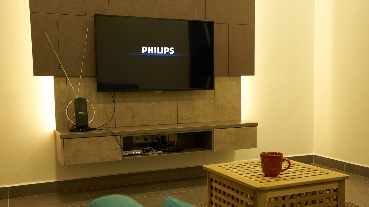 TV Philips instalada em painel de madeira na parede