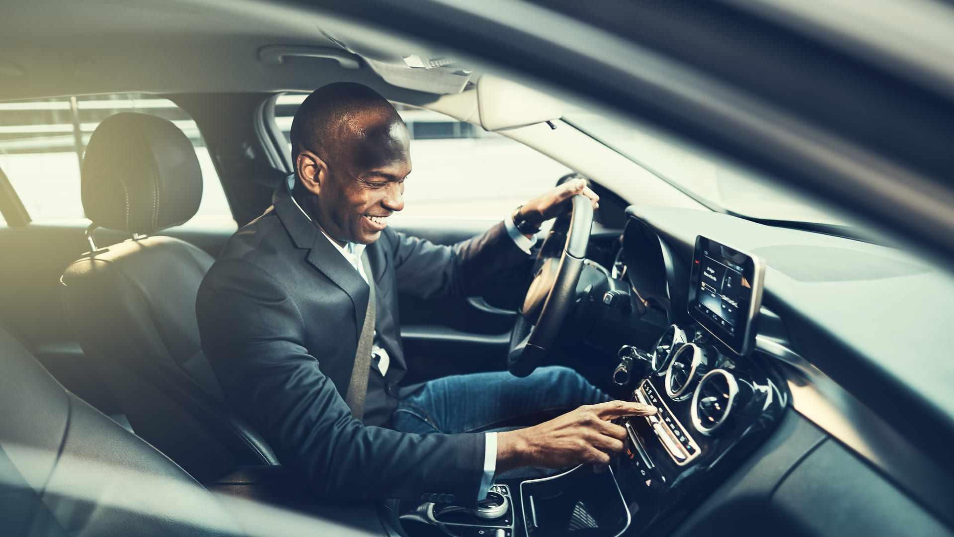 Homem negro sentado em seu carro configurando a sua central multimídia