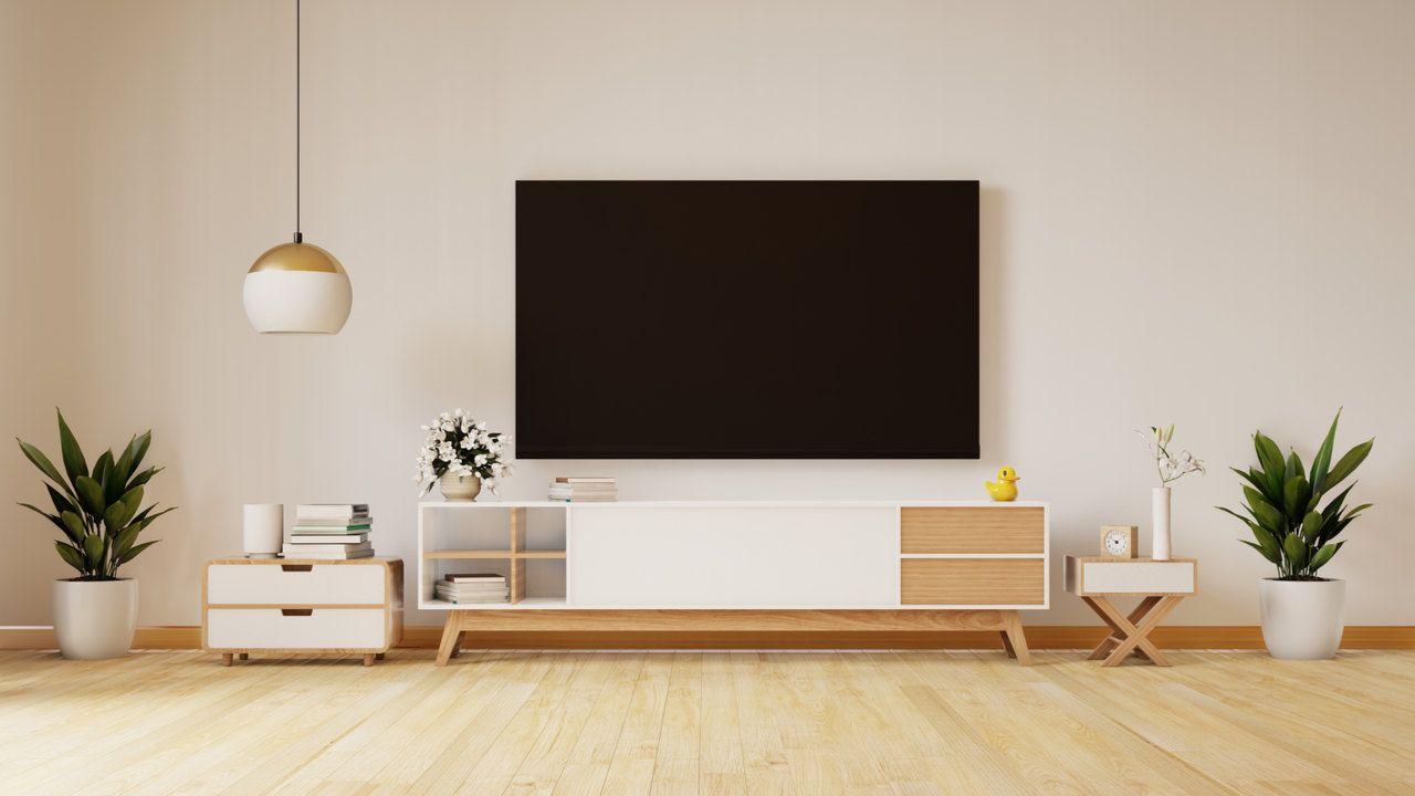 Sala de estar com rack de madeira e branco e TV plana pendurada na parede branca acima do rack