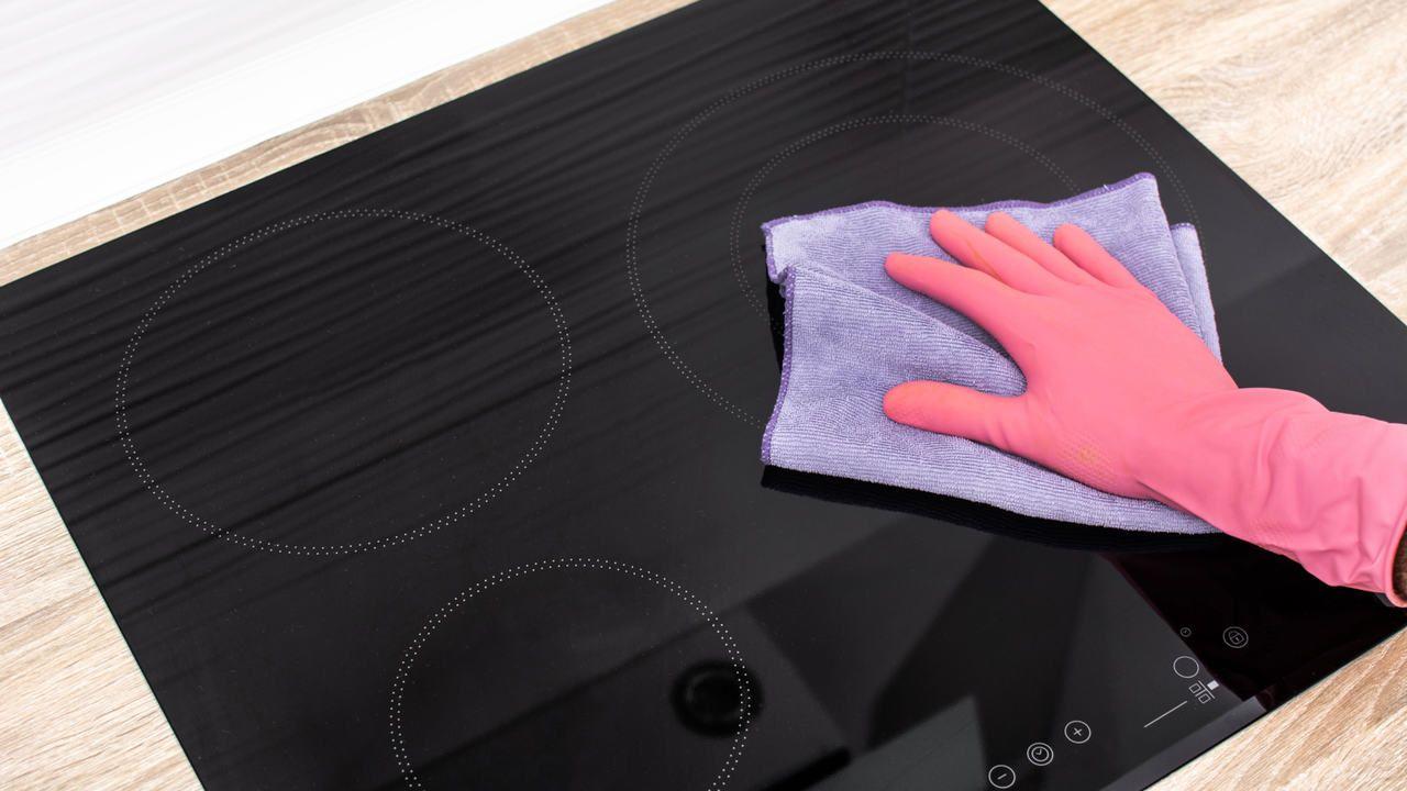 Mão com luva cor de rosa segurando um paninho lilás enquanto limpa um fogão de indução preto