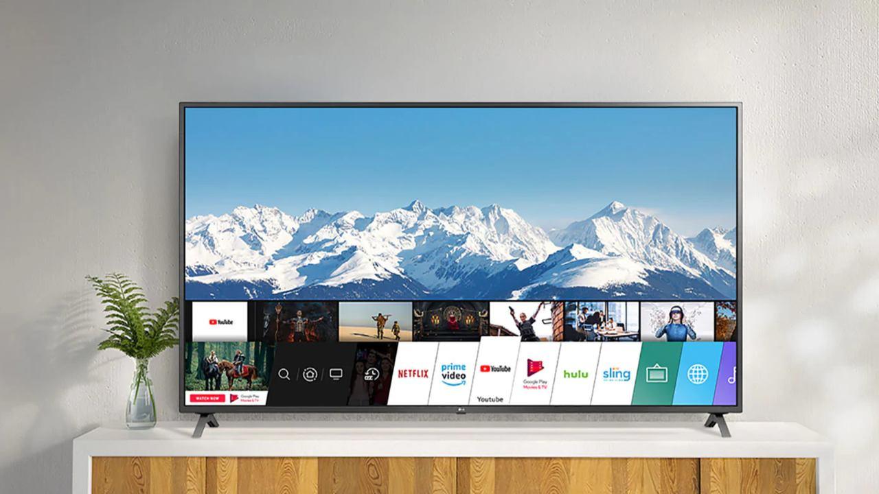 TV apoiada sobre móvel branco com menu inferior de aplicativos aberto na tela