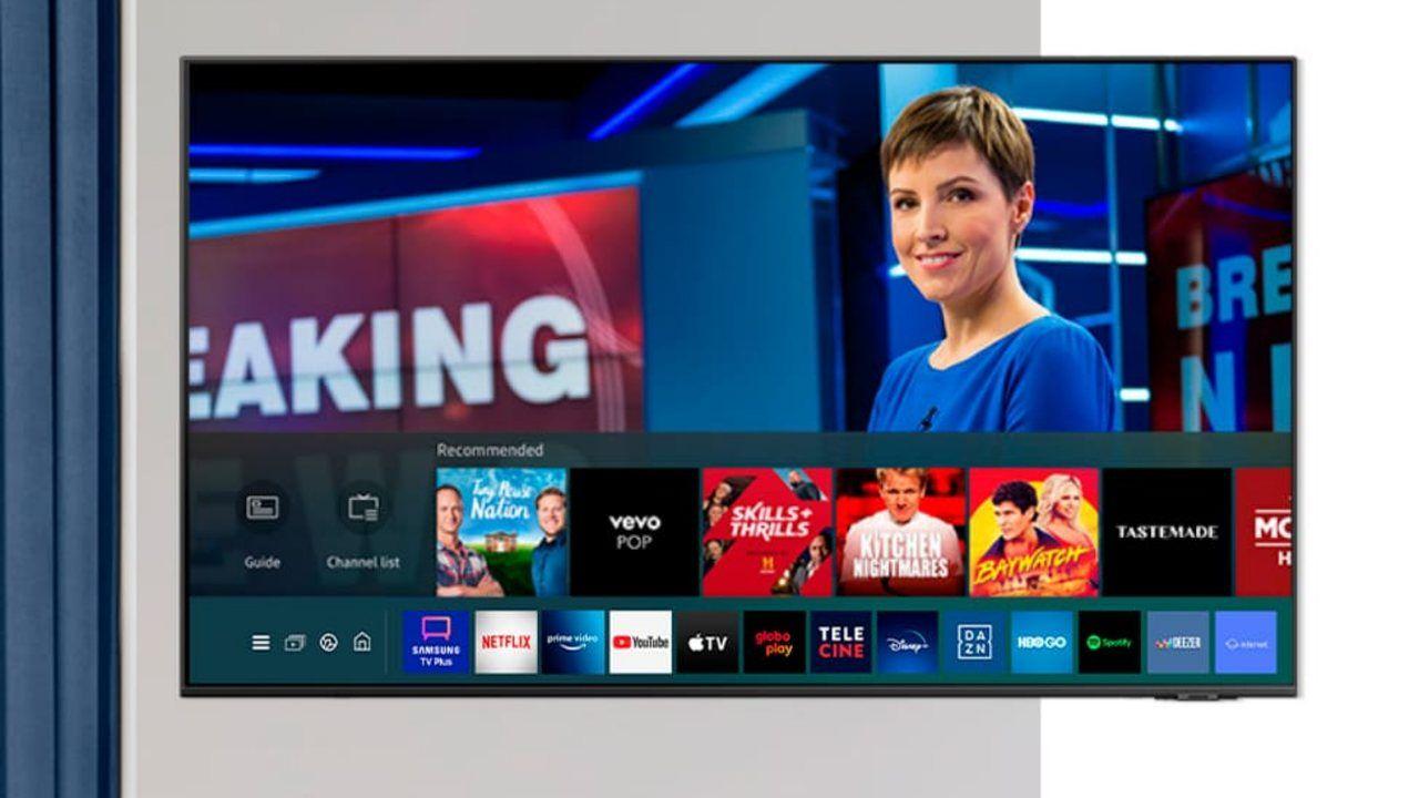 TV instalada em parede cinza com programa de notícias passando na tela e menu inferior de aplicativos aberto