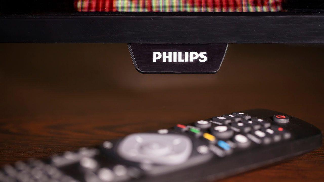 TV Philips com controle remoto, ambos apoiados em mesa de madeira