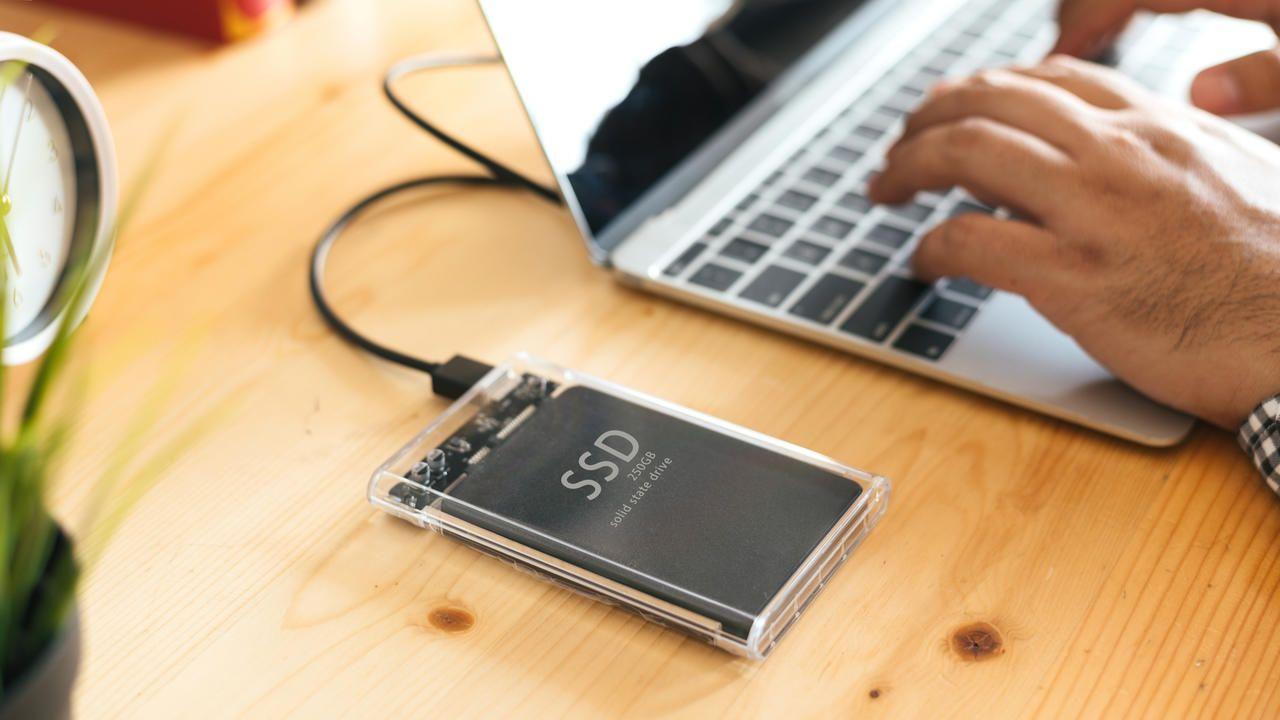 Homem utilizando SDD externo conectado ao notebook