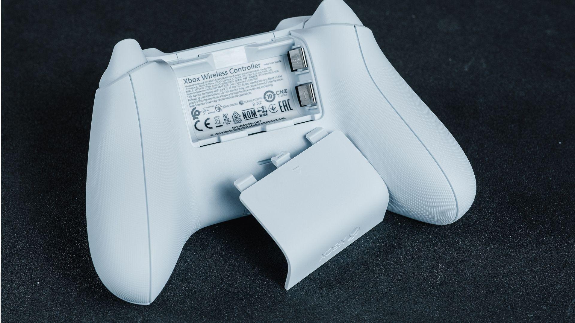 Parte de trás do controle xbox series x/s com compartimento de pilhas aberto