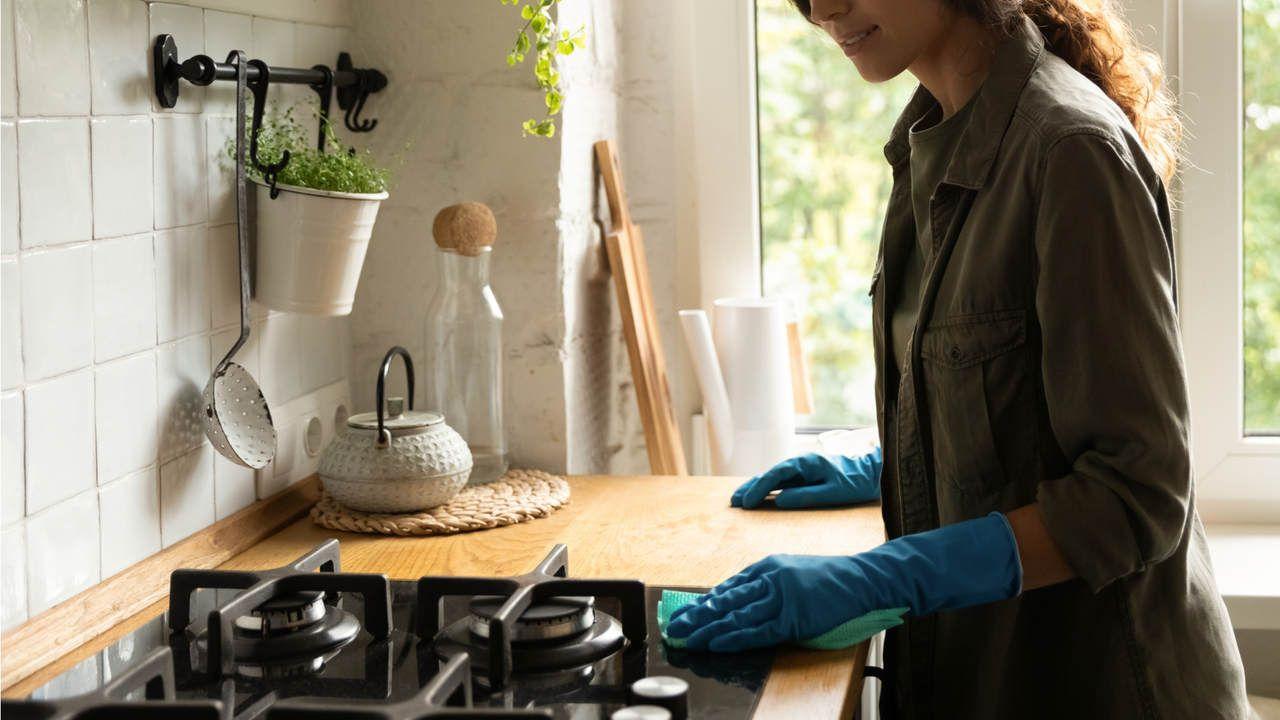 Mulher com luvas de borracha azuis limpando um fogão com mesa de vidro