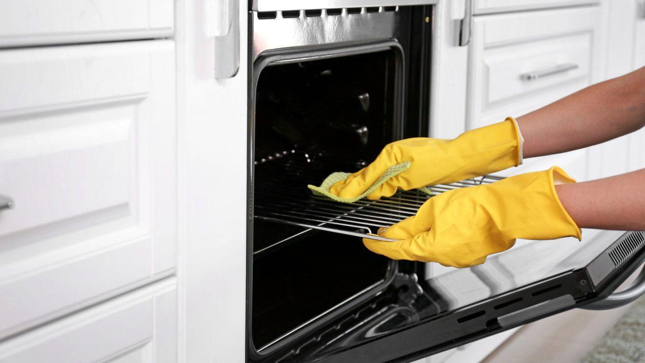 Mão usando luva de proteção amarela segurando grade de forno aberto, com esponja azul macia sobre a tampa