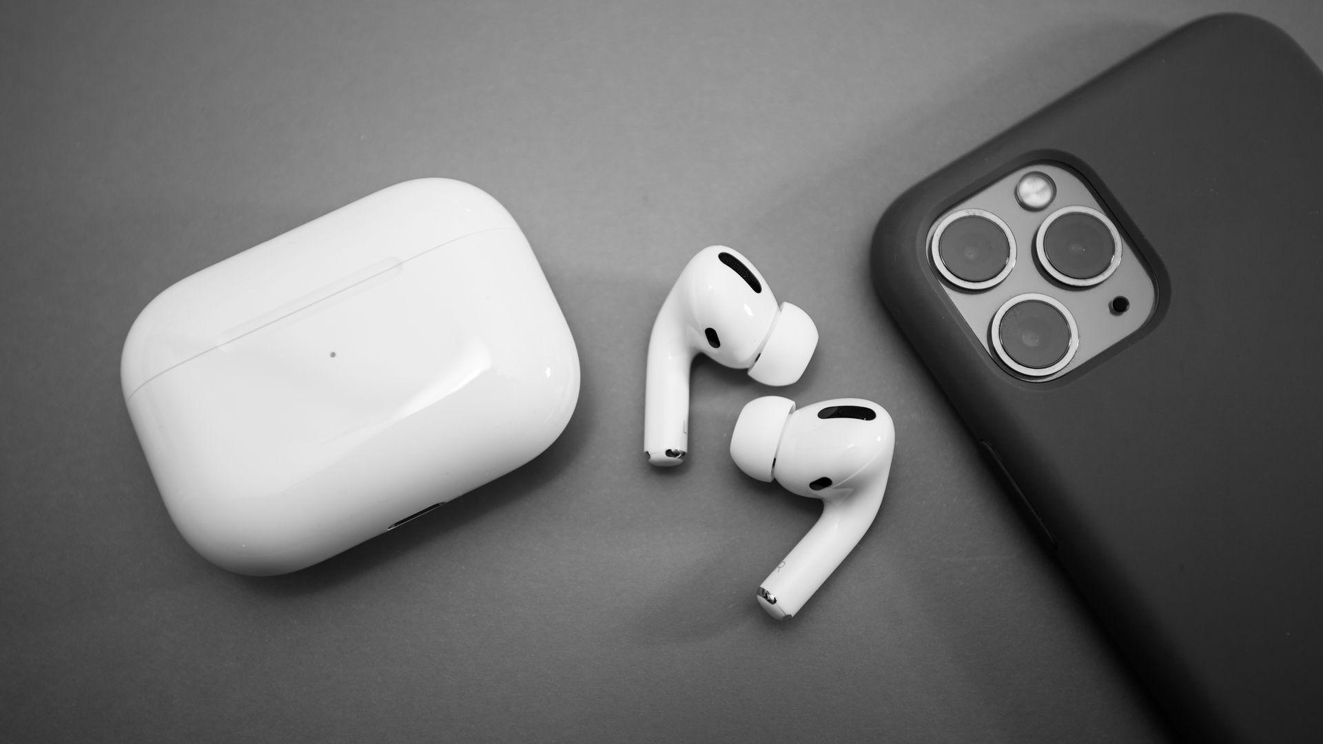 AirPods Pro ao lado do seu estojo e de um iPhone 11 Pro