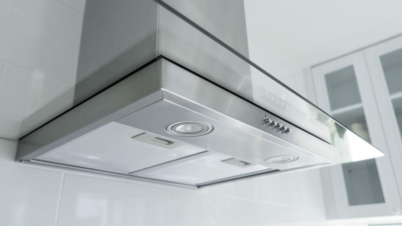 Depurador de ar de inox instalado em parede branca na cozinha