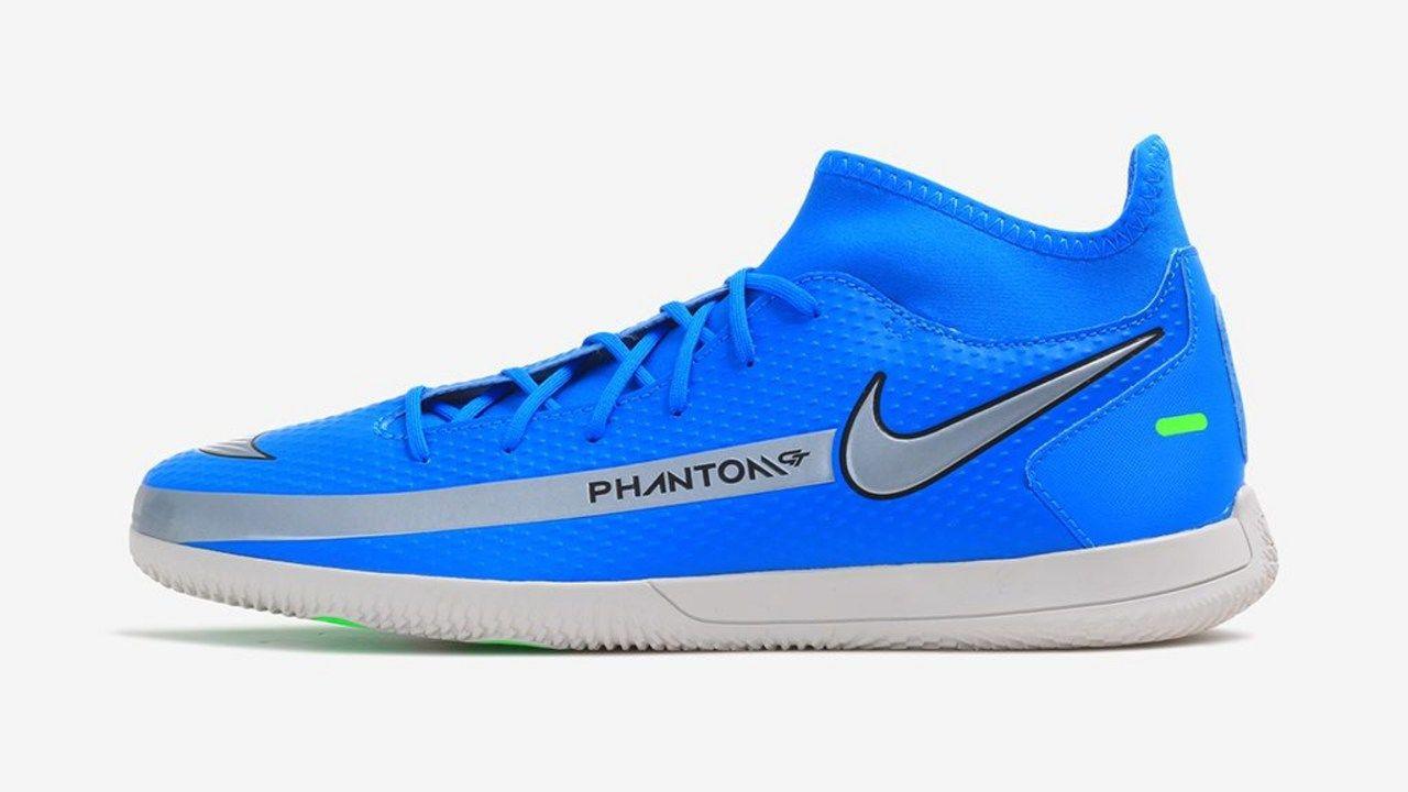 A chuteira Nike Phantom GT é azul com símbolo da Nike com contorno em preto. Os dizeres Phantom está em detalhe em uma faixa cinza.