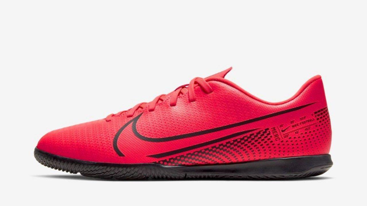 A chuteira Nike Mercurial Vapor 13 está em vermelho sob uma superfície branca. O símbolo da Nike é em preto vazado o fundo vemelho da chuteira.
