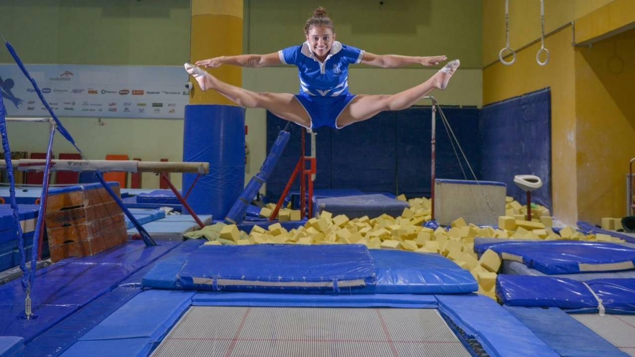 Mulher caucasiana pulando em cima de trampolim azul
