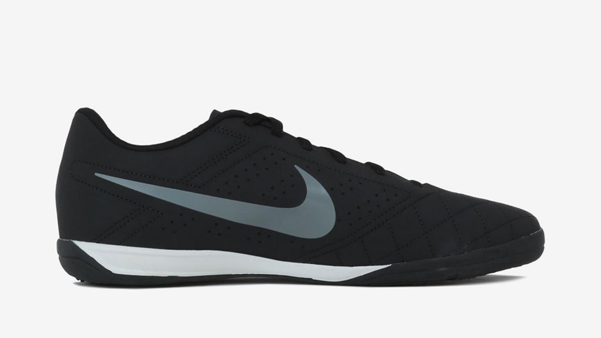 A chuteira Nike futsal Bec 2 preta está sob um superfície branca e tem solado branco, o simbolo da Nike é cinza.
