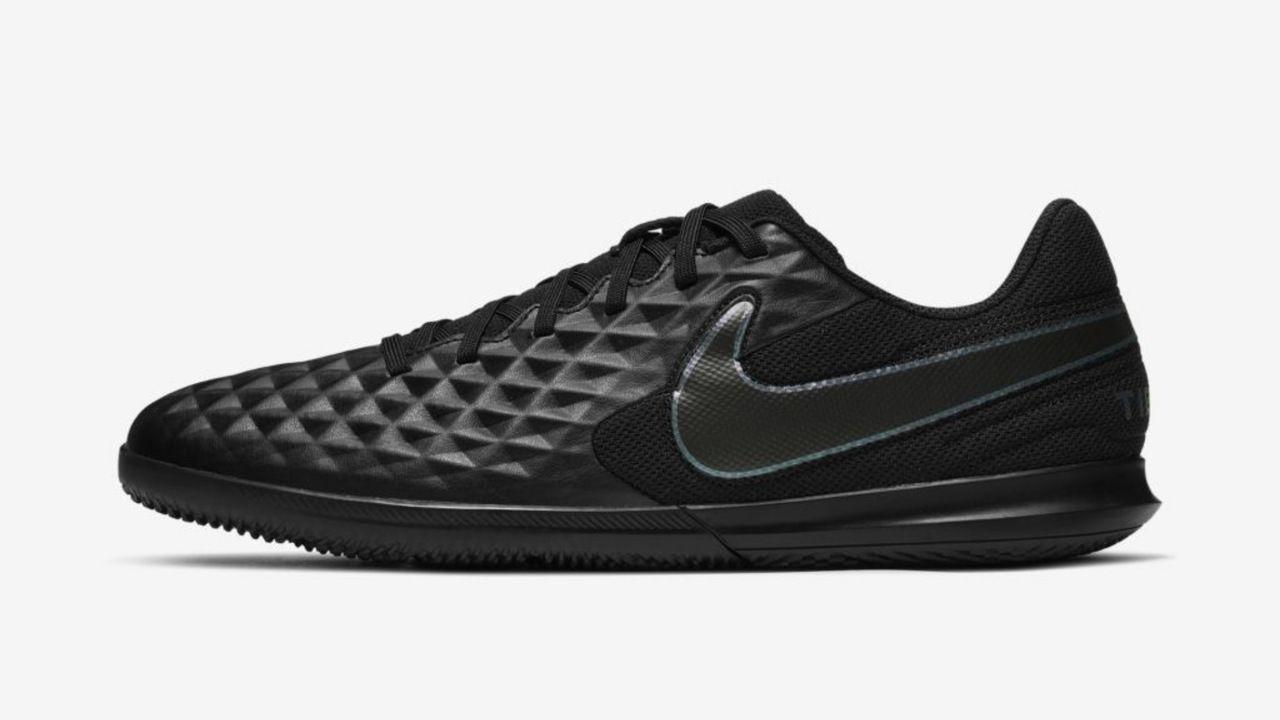 Chuteira Nike Tiempo Legend 8 Club preta tem relevos geométricos na parte da frente e está sob fundo branco.  O símbolo da Nike é na cor cinza escuro com contorno em prata