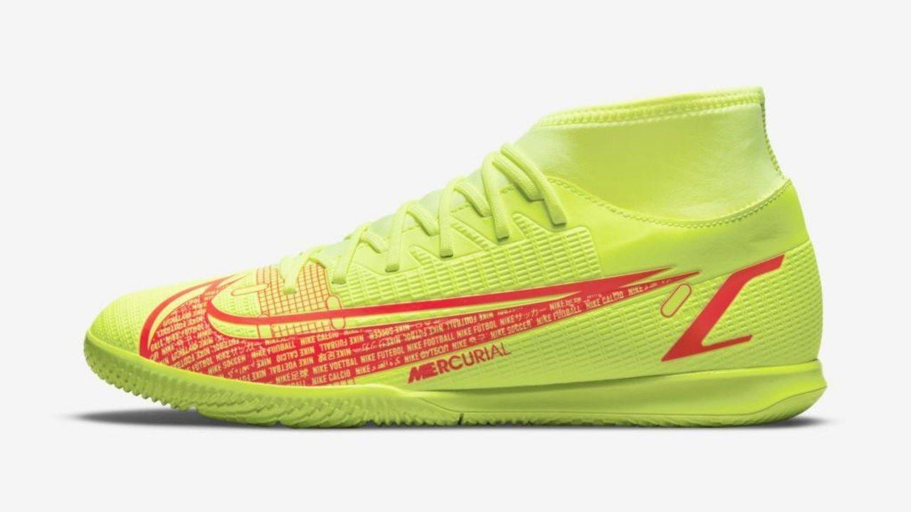 A chuteira Mercurial Superfly 7 Club está sob superfície branca. Ela é da cor amarelo fluorecente com cano medio. O símbolo da Nike é na cor vermelha com grafismos em branco.