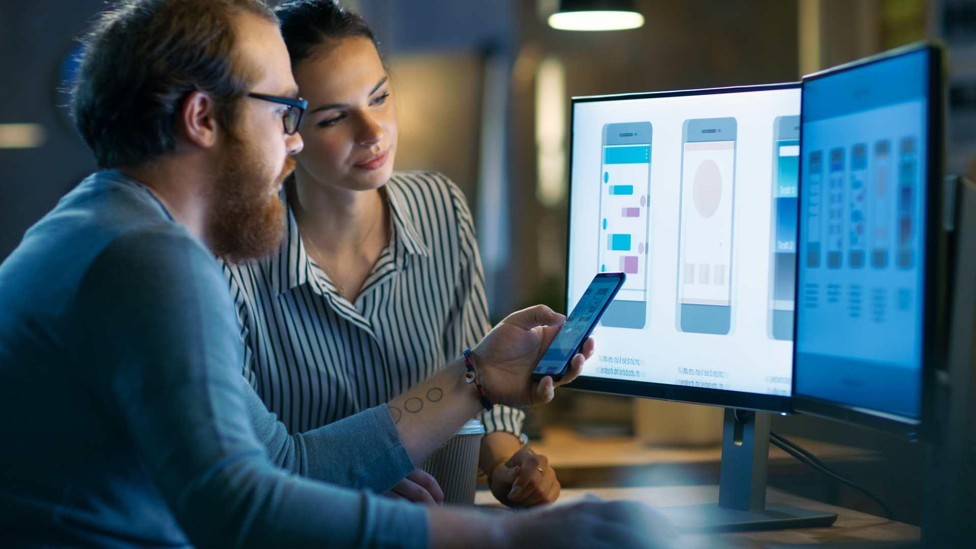 Homem e mulher aprendendo como criar um aplicativo em frente ao computador e celular