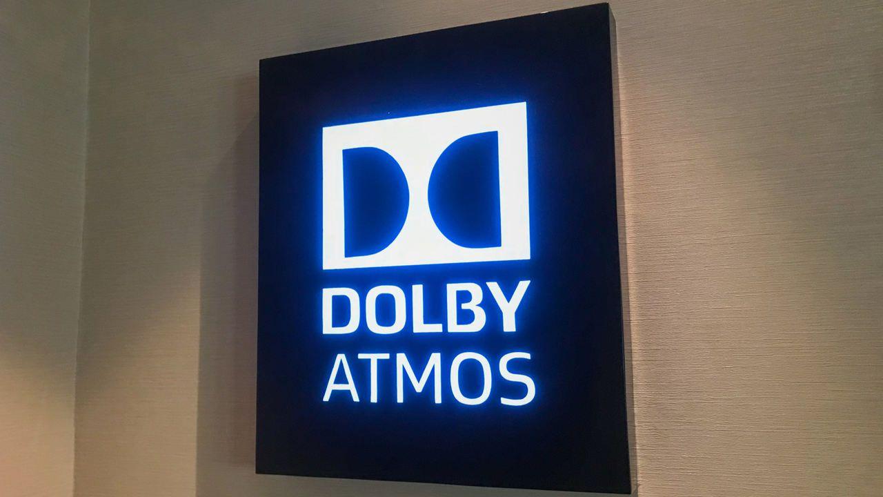 Placa retro iluminada pendurada em parede branca com o símbolo da tecnologia Dolby Atmos