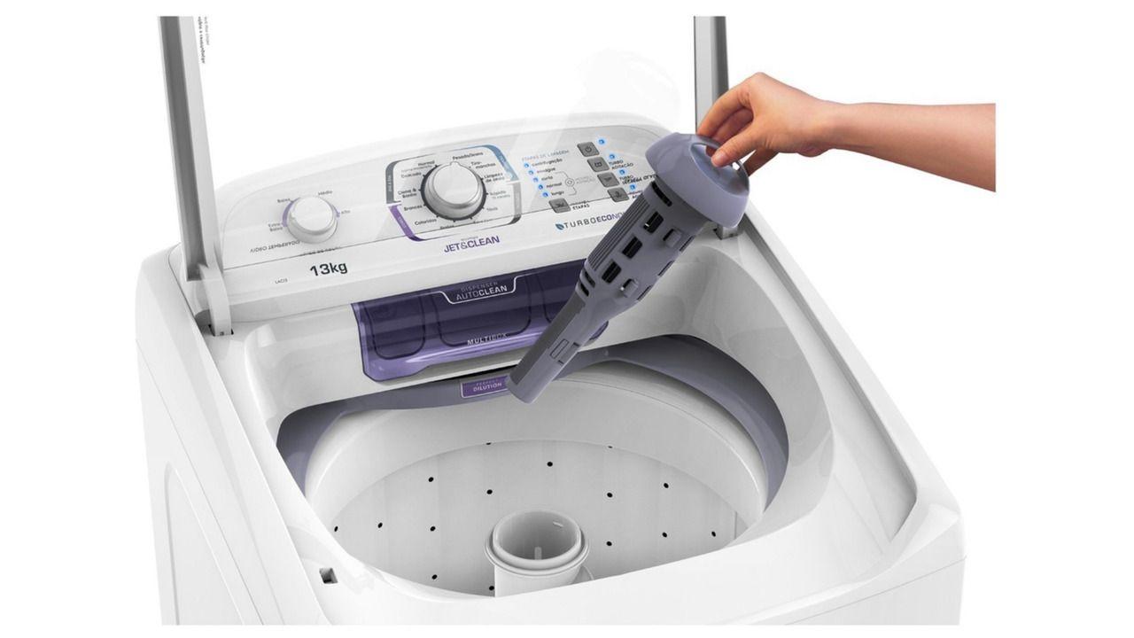 Parte de cima da lavadora Electrolux LAC13 com uma mão retirando o filtro da máquina