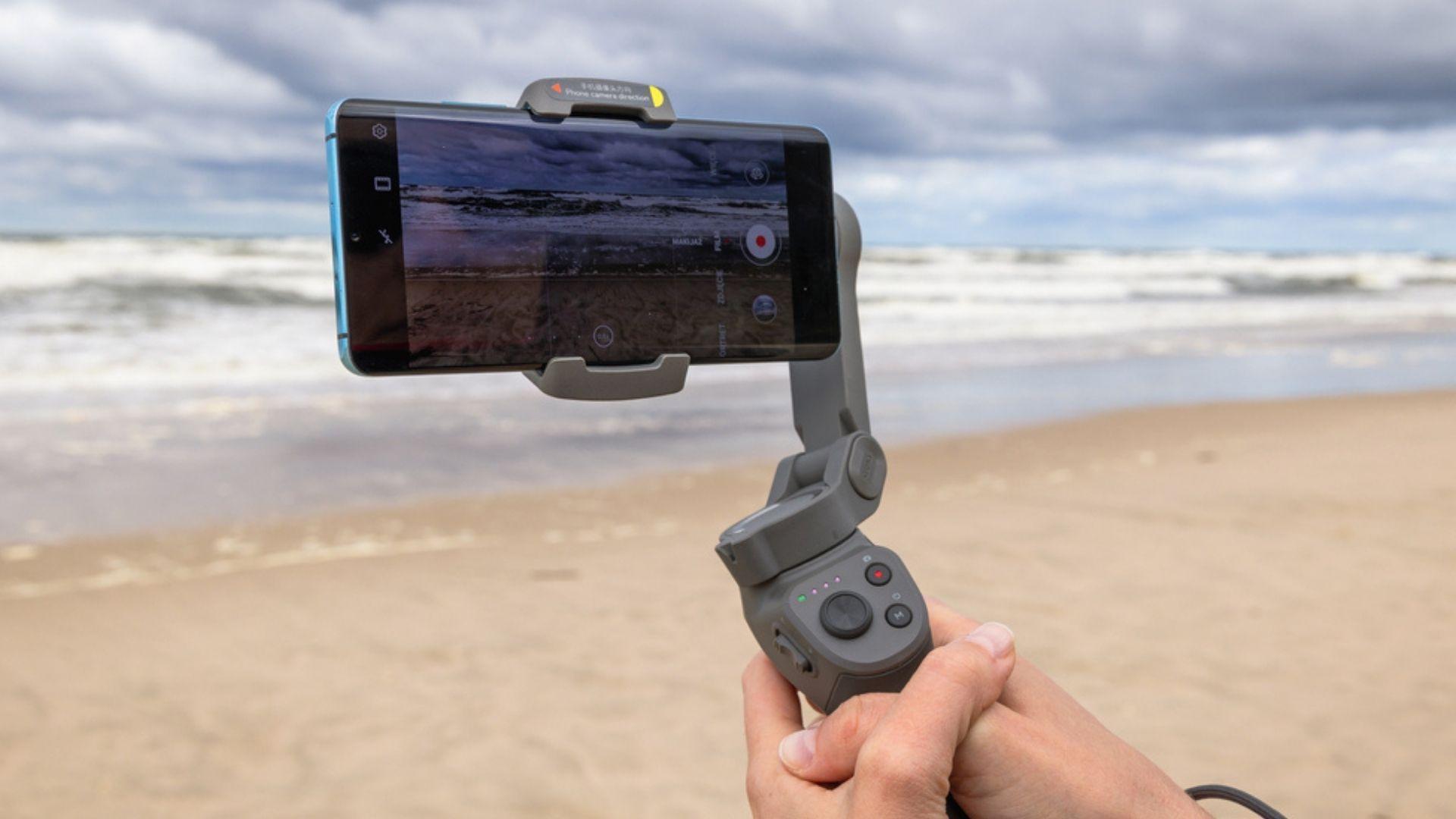 Pessoa segurando um estabilizador de celular em frente à praia