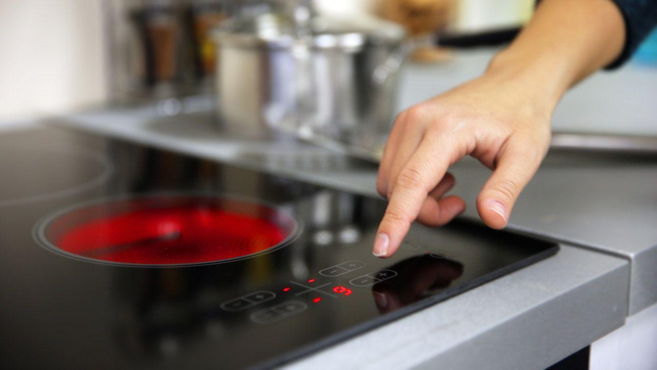 Mão ajustando a temperatura no painel touchscreen de um fogão de indução