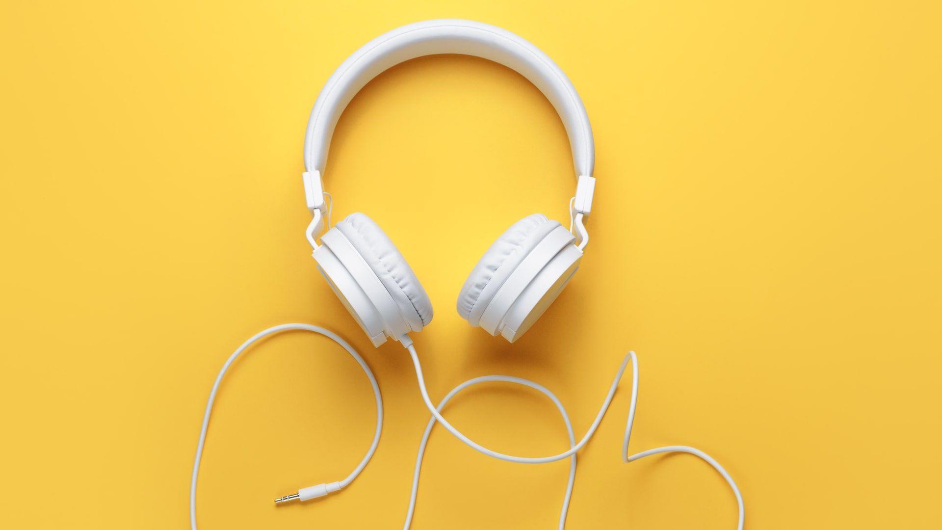 Fone de ouvido com fio no estilo headphone em um fundo amarelo