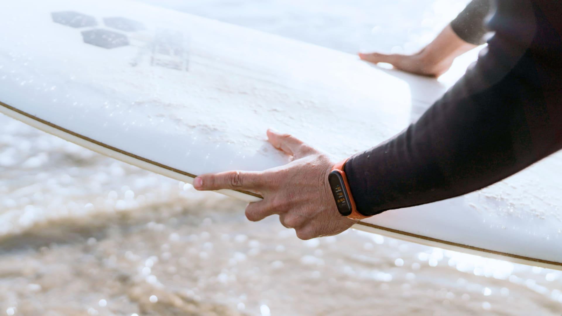 Amazfit Band 5 usada por surfista enquanto segura a prancha em direção ao mar