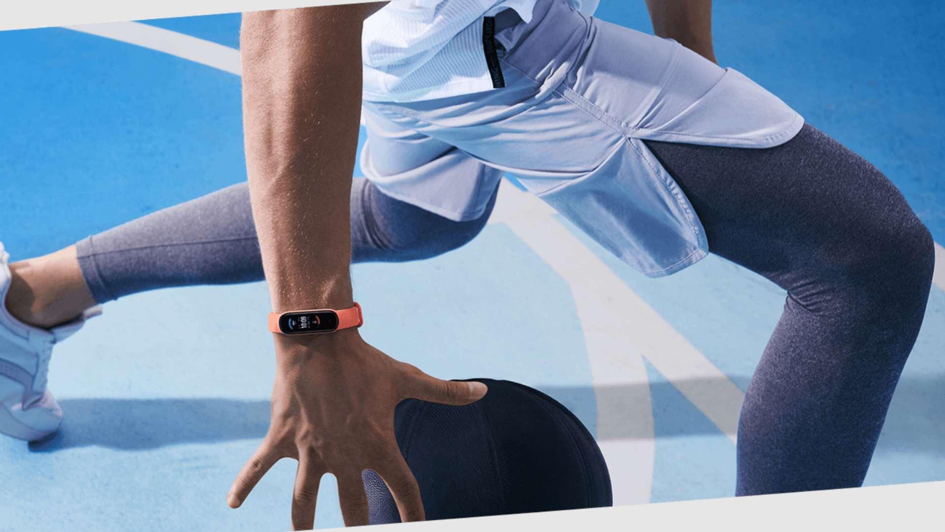 Homem com roupa esportiva usa Amazfit Band 5 laranja enquanto joga basquete na quadra azul