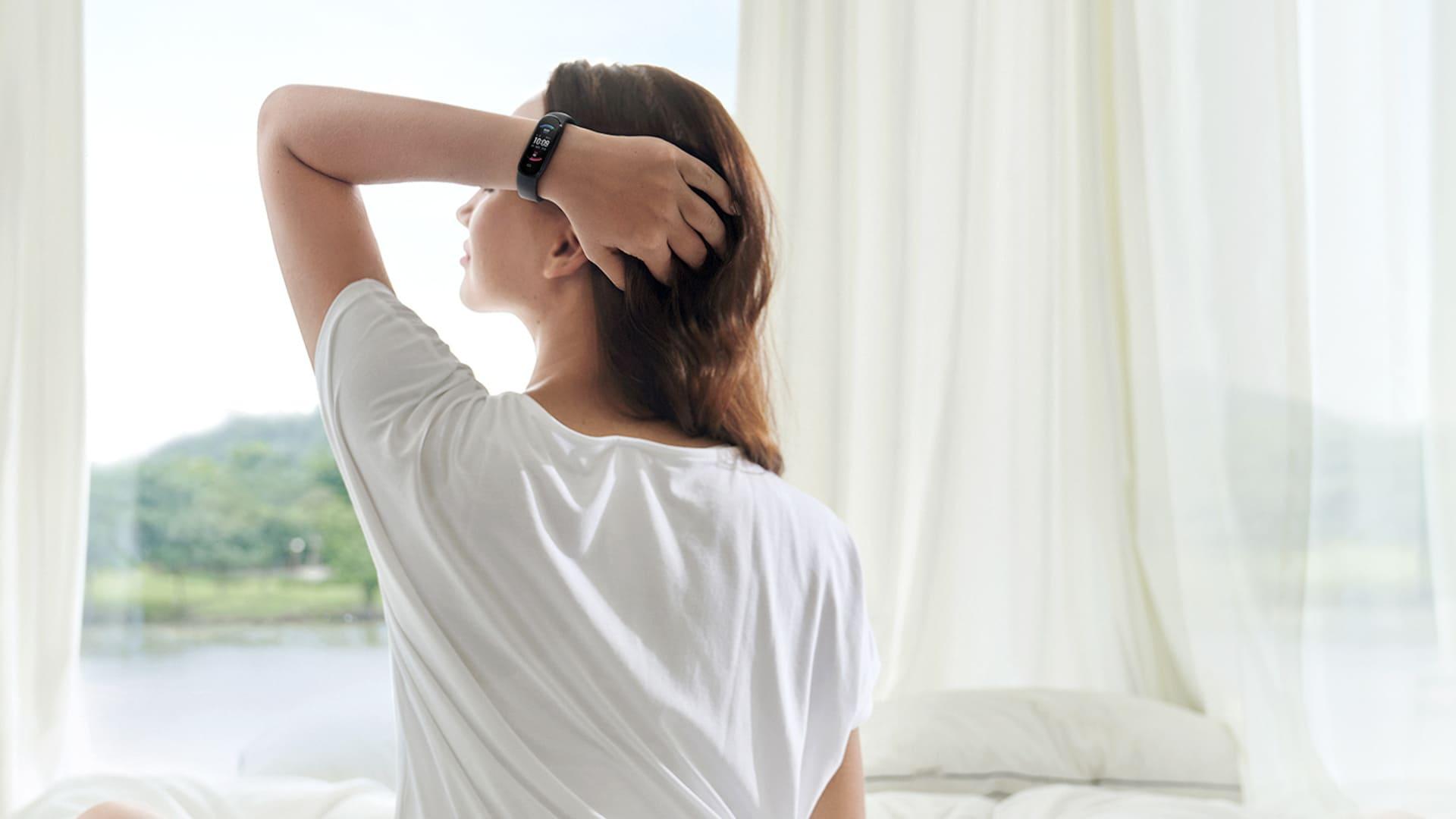 Mulher de costas usa Amazfit Band 5 no quarto enquanto segura o cabelo e aproveita o bem-estar