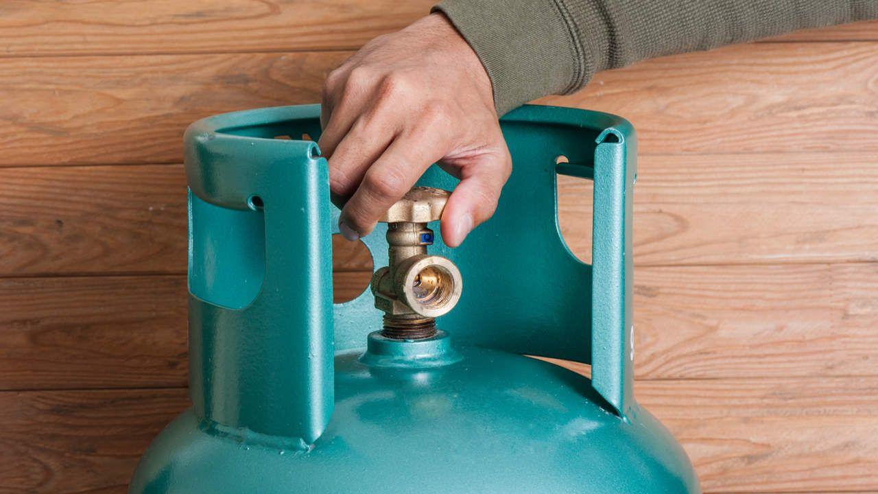 Botijão de gás azul claro com mão segurando o registro