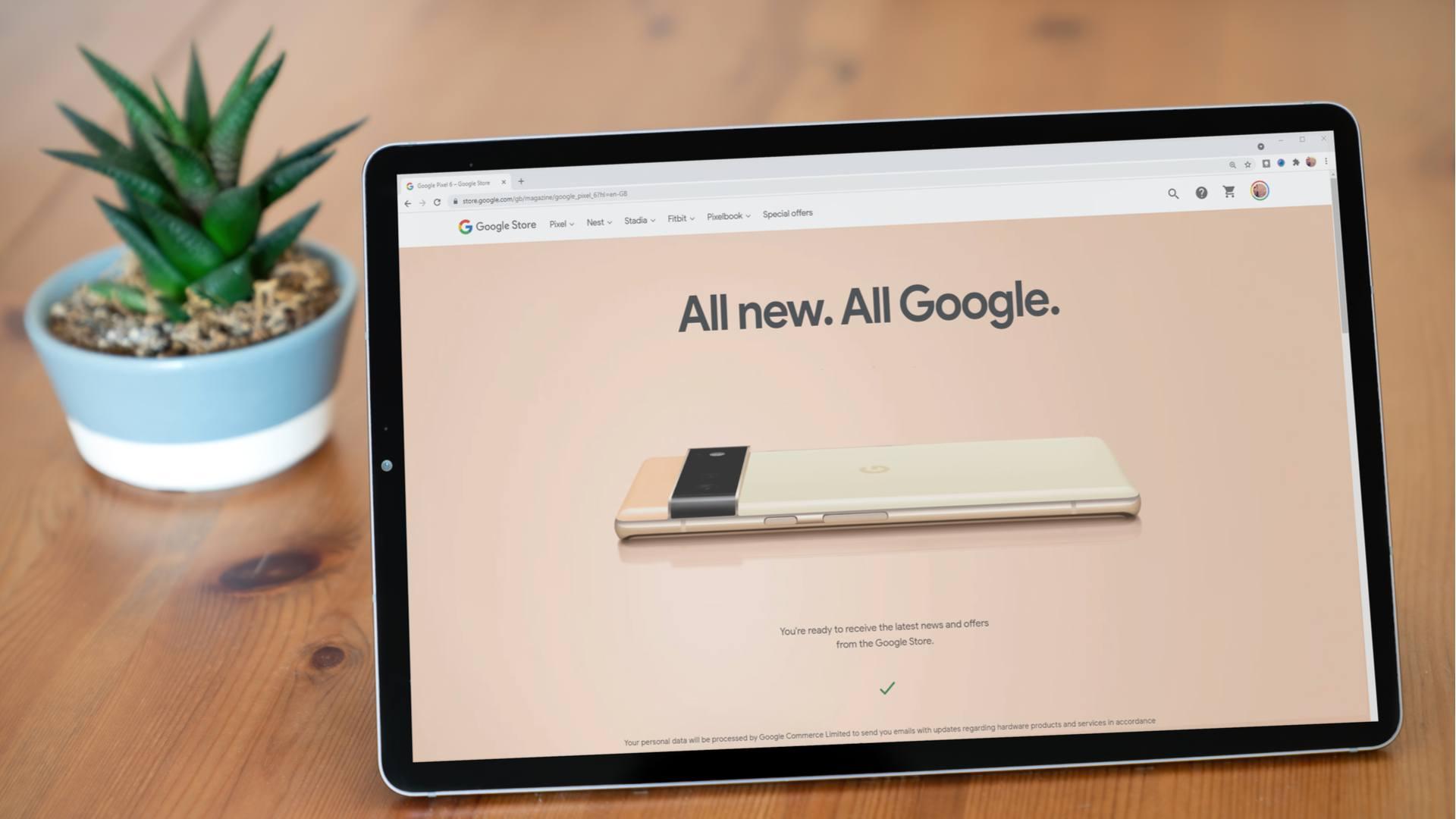Tablet com imagem do novo Google Pixel 6 em cima de mesa ao lado de vaso de planta