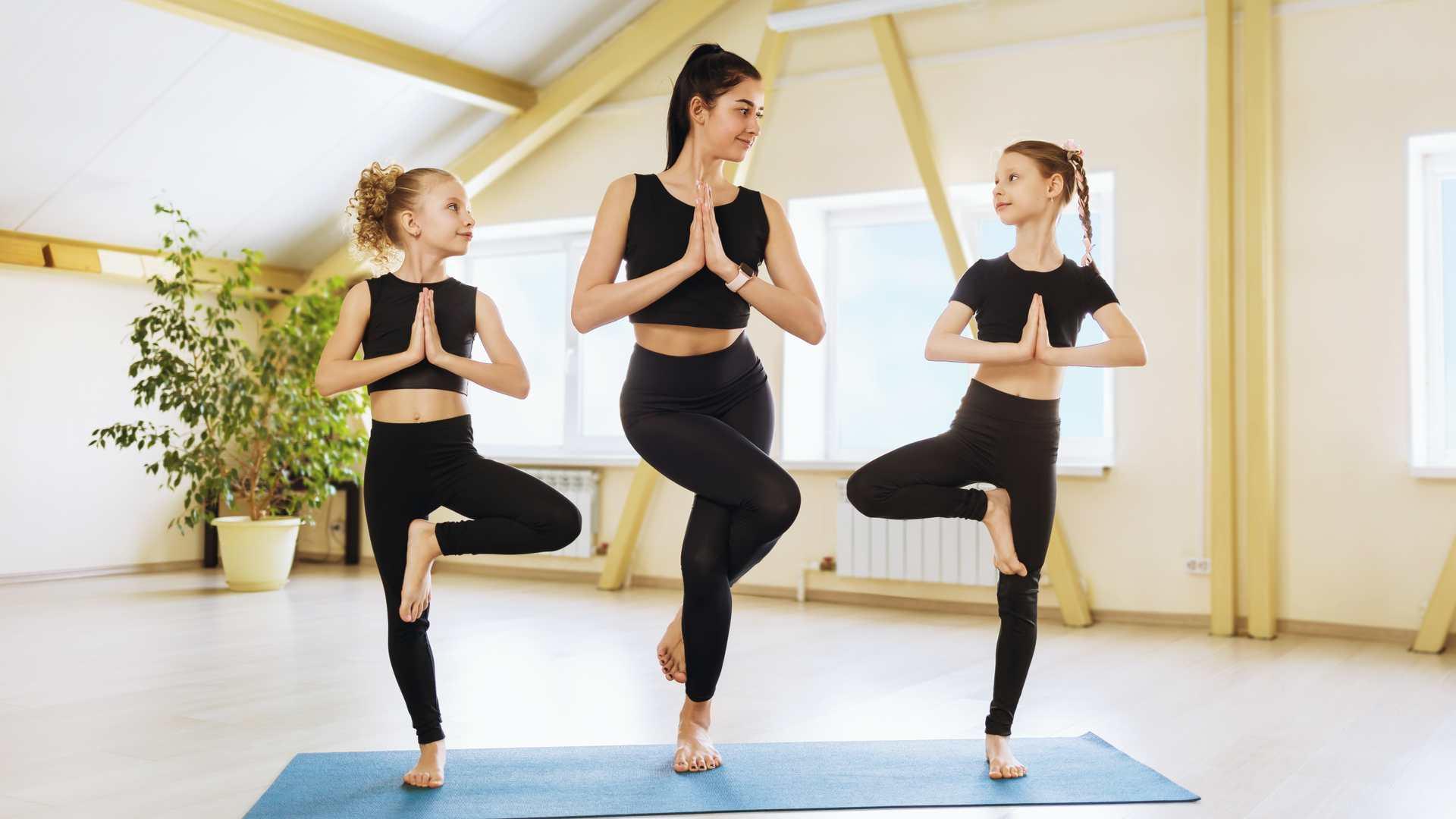 Professora de yoga dando aula para duas meninas crianças