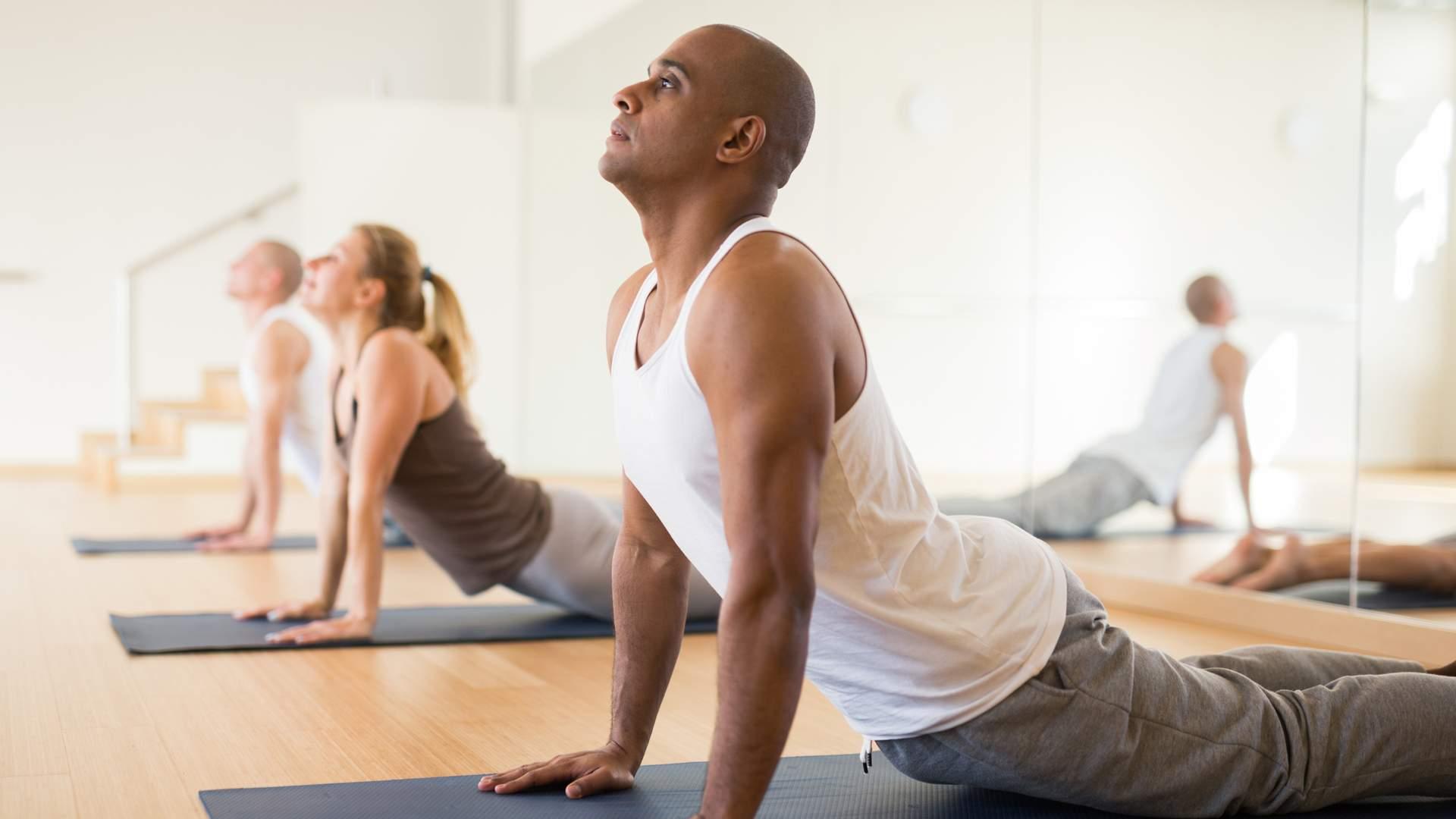 Homem fazendo yoga em aula no estúdio