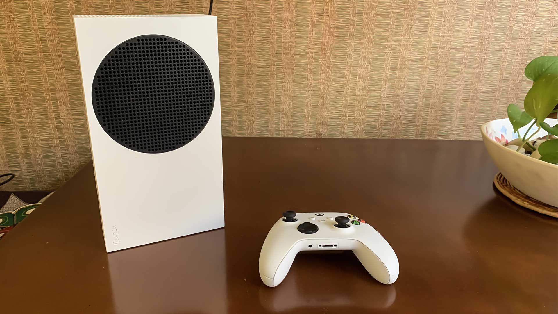 Xbox Series S em pé, de lado, ao lado de controle
