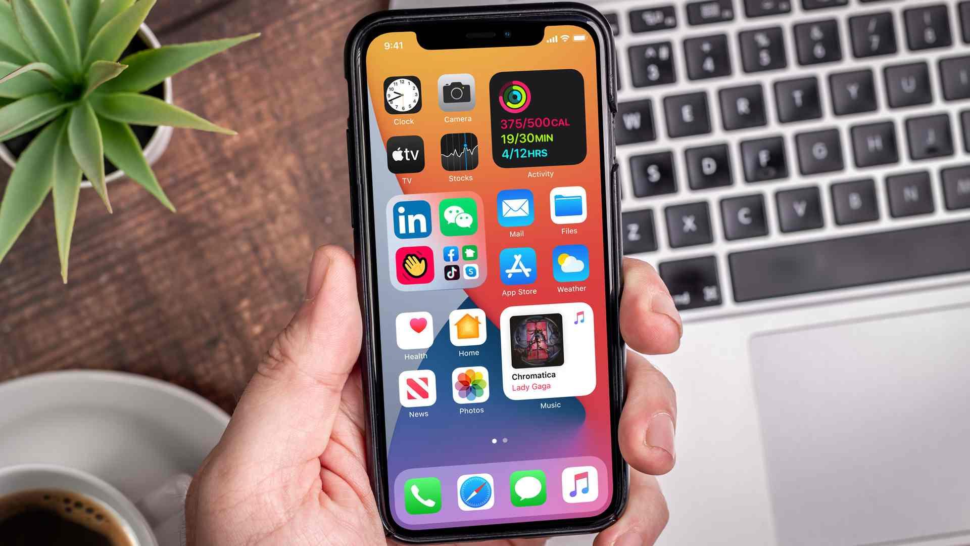 Pessoa segurando um iPhone com recursos do iOS na tela