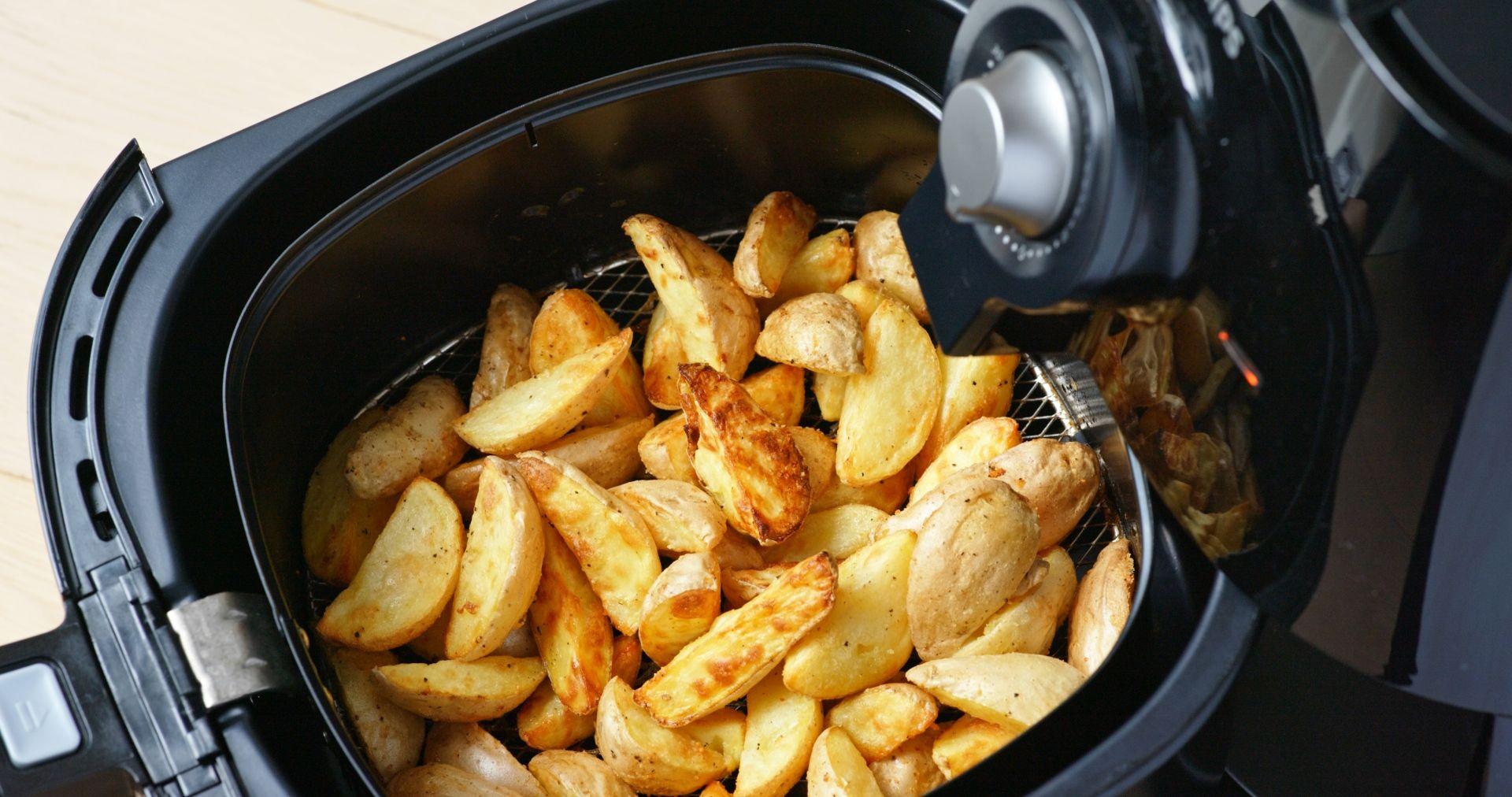 Cesto de airfryer aberto com batatas fritas cortadas em meia lua
