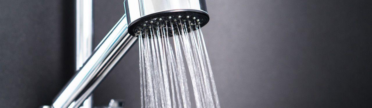 Chuveiro de inox ligado com água corrente