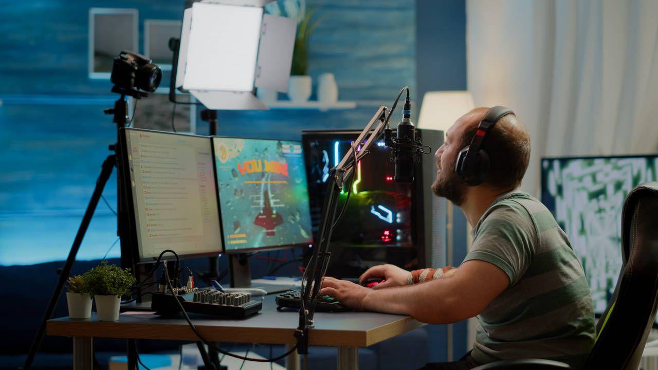 Homem utilizando um microfone gamer enquanto joga partida no computador