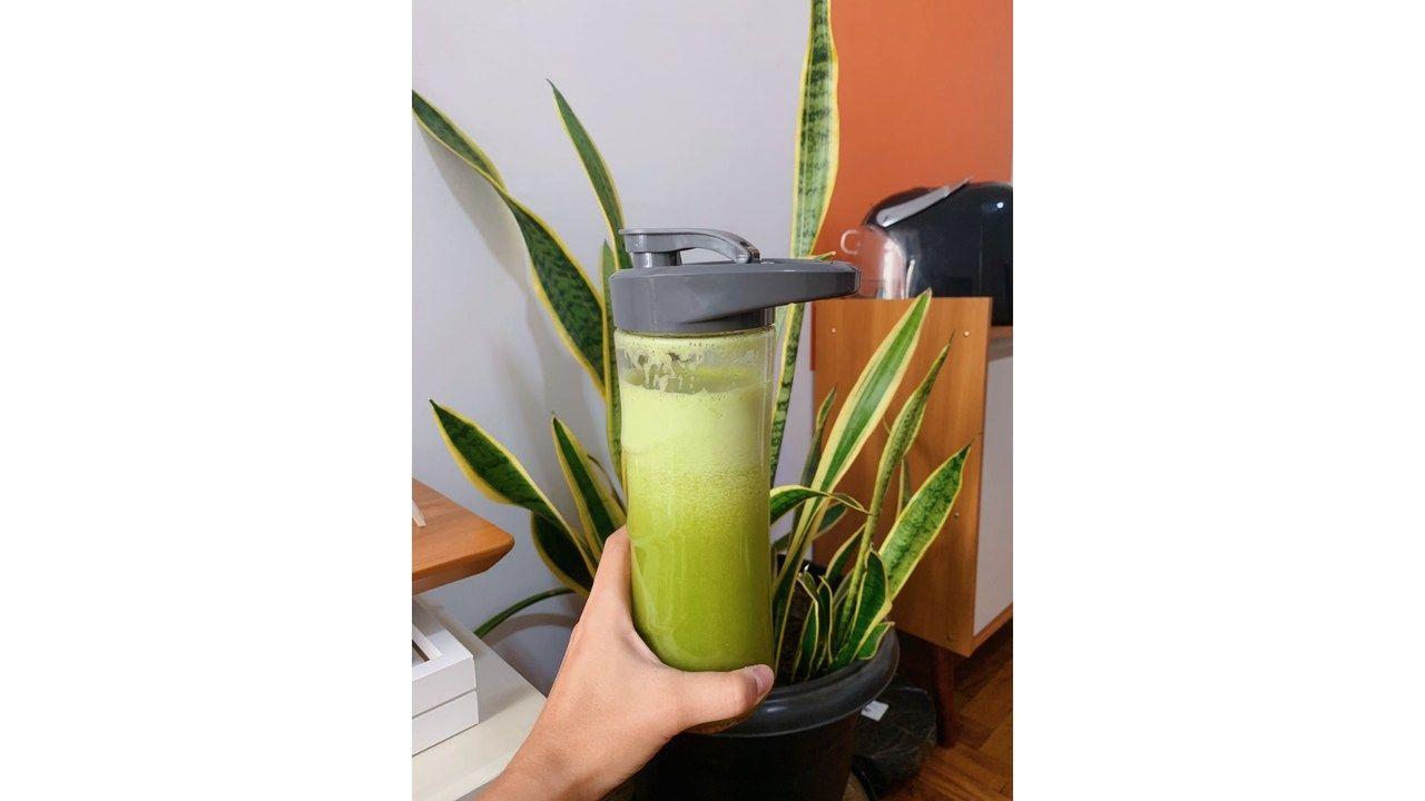 Mão segurando o copo do liquidificador Black & Decker com o suco verde dentro