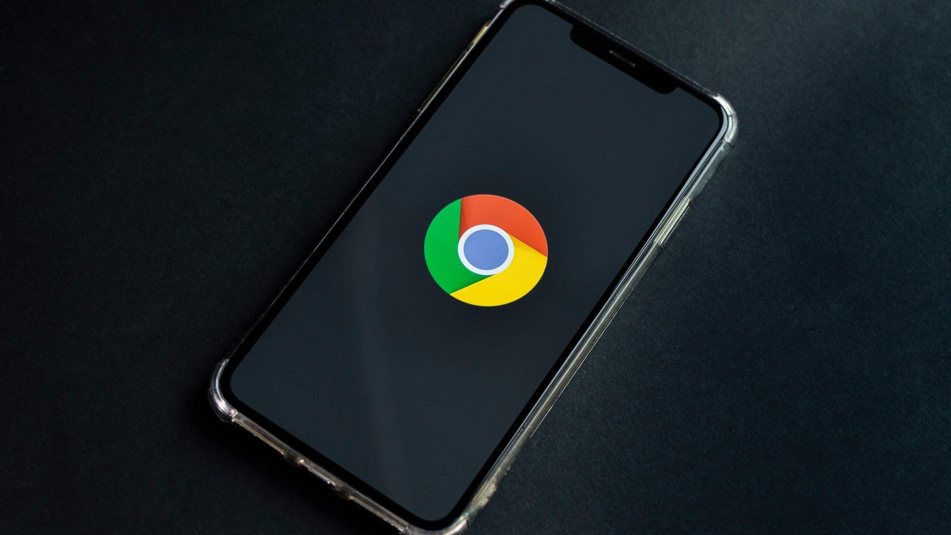 Celular com modo escuro do Chrome em um fundo preto