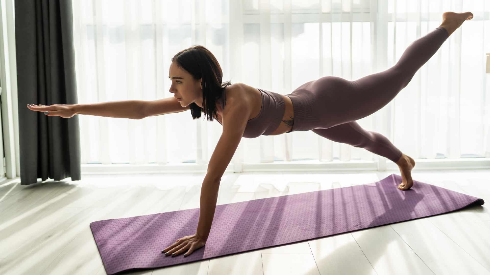 Mulher fazendo aula de yoga em casa