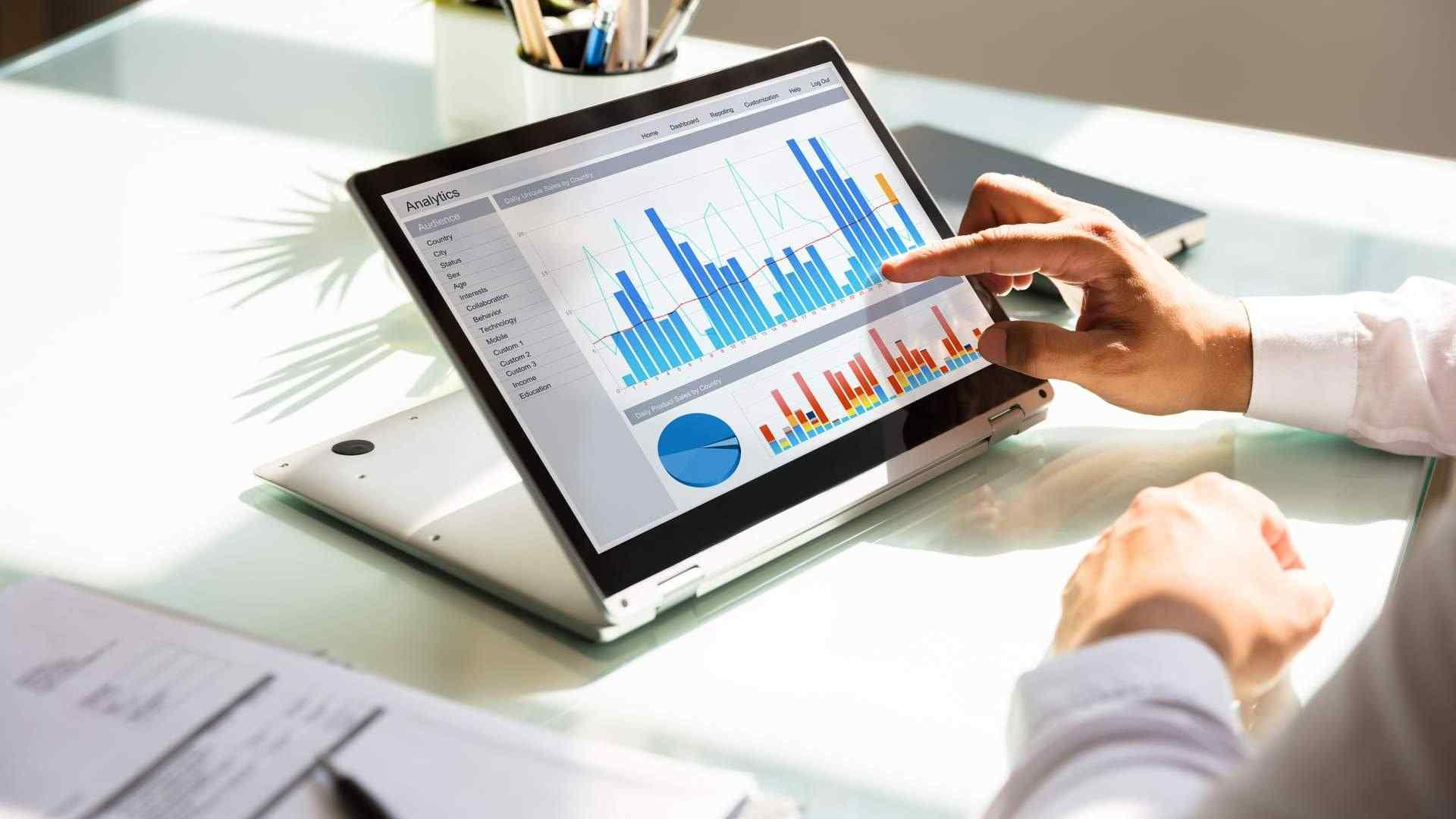 Homem observando gráficos empresariais em notebook 2 em 1 dobrado para trás